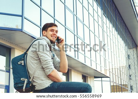 Man with bag talking at phone in airport. #556558969