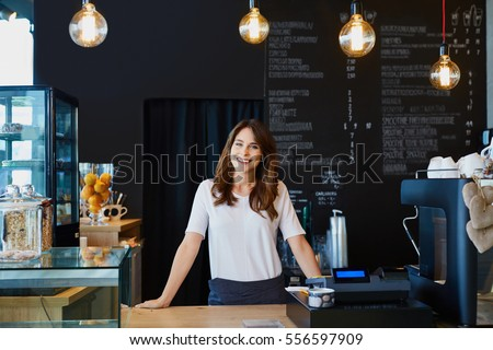 Young female barista standing behind the bar in cafe smiling Royalty-Free Stock Photo #556597909