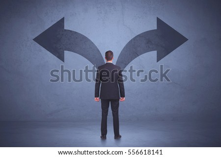 Businessman taking a decision while looking at arrows on the wall concept background #556618141
