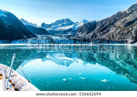 Cruise ship in Glacier Bay cruising towards Johns Hopkins Glacier in Alaska, USA. Panoramic view during summer. Royalty-Free Stock Photo #556662694