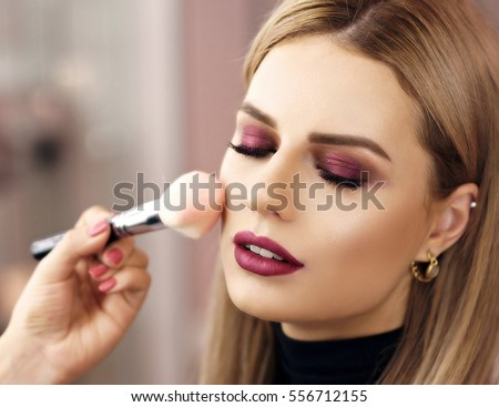 Process of making makeup. Make-up artist working with brush on model face. Portrait of young blonde woman in beauty saloon interior. Applying tone to skin. #556712155