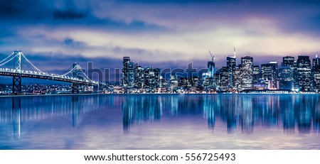 Night view of beautiful San Francisco California city skyline with lit buildings, bay and bridge,