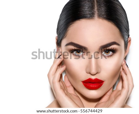 Gorgeous Young Brunette Woman face portrait. Beauty Model Girl with bright eyebrows, perfect make-up, red lips, touching her face. Sexy lady makeup for party. Isolated on white background #556744429