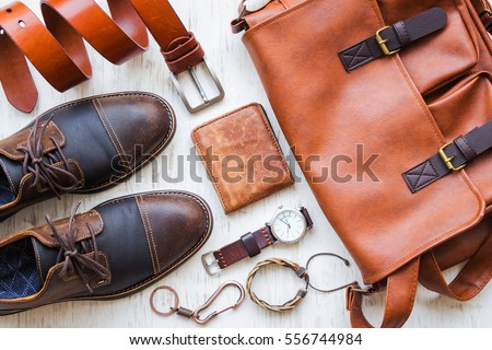 Men's casual outfits with leather accessories on white rustic wooden background, lifestyle traveler, beauty and fashion concept Royalty-Free Stock Photo #556744984