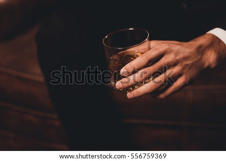 Close up of man's hand holding class of whiskey #556759369
