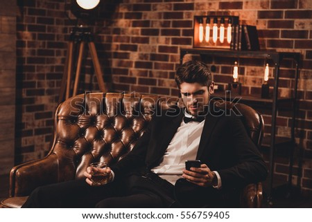 Young man in suit sitting on couch with glass of cognac and typing message #556759405