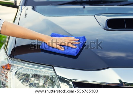 Asian woman's hand wiping surface of car by micro fiber cloth. #556765303