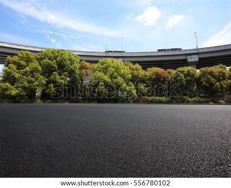Empty road floor surface with city viaduct overpass bridge background #556780102
