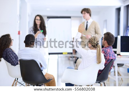 Businessman giving a presentation to his colleagues at work standing in front of a flipchart #556802038