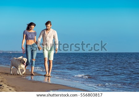 two young people running on the beach kissing and holding tight with dog #556803817