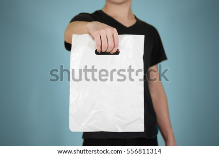 Man shows white blank plastic bag mock up isolated. Empty white polyethylene package mockup. Consumer pack ready for logo design or identity presentation. Commercial product food packet handle #556811314