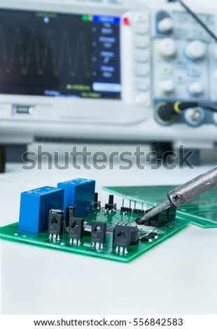 Electronic working place with soldering iron and circuit board #556842583