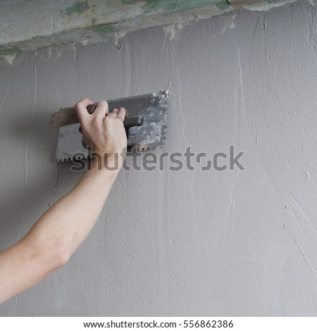 Hands Plasterer at work. Application of the plaster on the wall. textured plaster #556862386