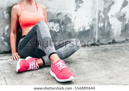 Fitness sport woman in fashion sportswear doing yoga fitness exercise in the city street over gray concrete background. Outdoor sports clothing and shoes, urban style. Sneakers closeup. #556889644