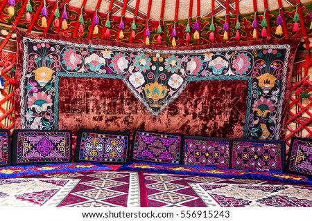 Traditional carpet, rug and pillow treatment details in the interior of a nomadic yurt #556915243