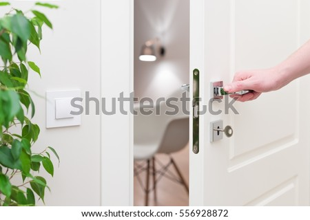 To open the door. Modern white door with chrome metal handle and a man's arm. Elements of interior closeup Royalty-Free Stock Photo #556928872