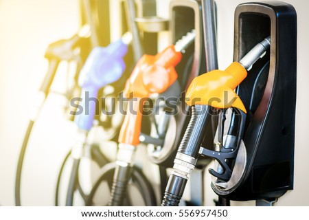 Colorful Petrol pump filling nozzles isolated on white background , Gas station in a service in warm sunset  Royalty-Free Stock Photo #556957450