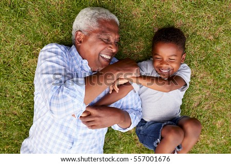 Grandfather and grandson play lying on grass, aerial view