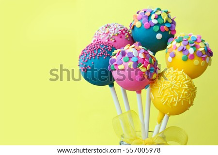 Colorful cake pops on a yellow background Royalty-Free Stock Photo #557005978