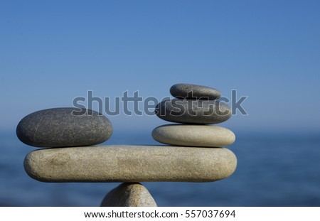 Balance of stones. To weight pros and cons. Balancing stones on a blue sky and sea background with a copy space. Scales. Close up. #557037694