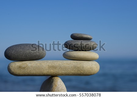 Balance of stones. To weight pros and cons. Balancing stones on a blue sky and sea background with a text space. Scales. Close up..... #557038078