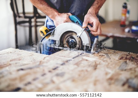 Carpenter using circular saw for cutting wooden boards. Construction details of male worker or handy man with power tools Royalty-Free Stock Photo #557112142