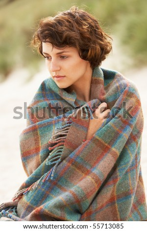 Young Woman Standing In Sand Dunes Wrapped In Blanket #55713085
