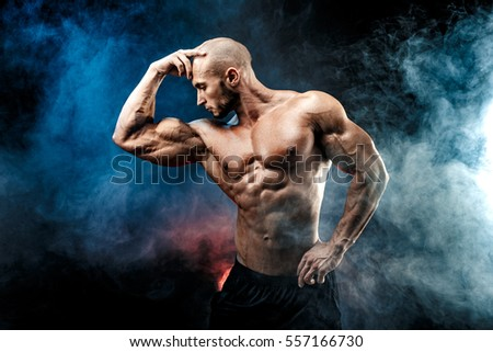 Strong bald bodybuilder with six pack. Bodybuilder man with perfect abs, shoulders,biceps, triceps and chest, personal fitness trainer flexing his muscles in blue, red smoke  #557166730