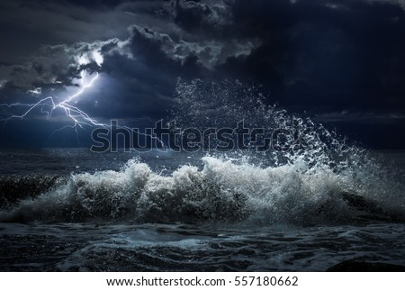 dark ocean storm with lgihting and waves at night Royalty-Free Stock Photo #557180662