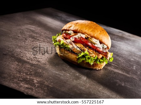 Studio shot of burger with chicken on metal or stone dark surface and black background #557225167