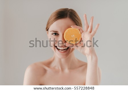 Healthy eating makes you beautiful. Attractive young woman with freckles on face holding orange slice and smiling while standing against background #557228848