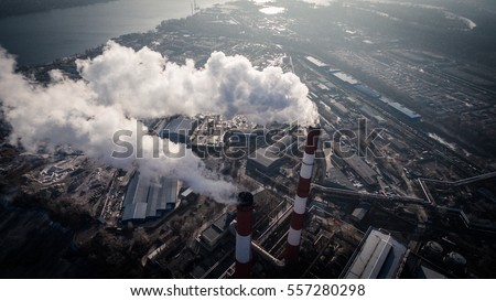 Air pollution by smoke coming out of two factory chimneys. Industrial zone in the city. Kiev, Ukraine, aerial view #557280298