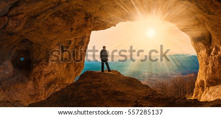 Beautiful amazing sunset. Mountains in north country Russia Caucasus. Unique landscape mainsail. Silhouette of a man. Old cave. Active sport and hobby. Spelunking background. Quest Royalty-Free Stock Photo #557285137