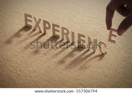 EXPERIENCE wood word on compressed or cork board with human's finger at E letter. Royalty-Free Stock Photo #557306794
