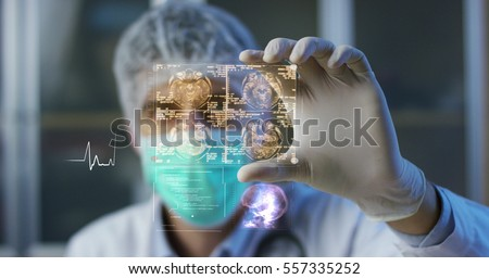 A physician, surgeon, examines a technological digital holographic plate represented the patient's body, the heart lungs, muscles, bones. Concept: Futuristic medicine, world assistance, and the future #557335252