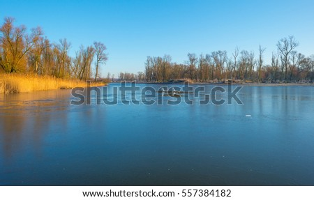 Shore of a frozen lake at sunrise in winter #557384182