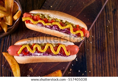 Hot Dog With Yellow Mustard, Onion, Pickles and French Fries Royalty-Free Stock Photo #557405038