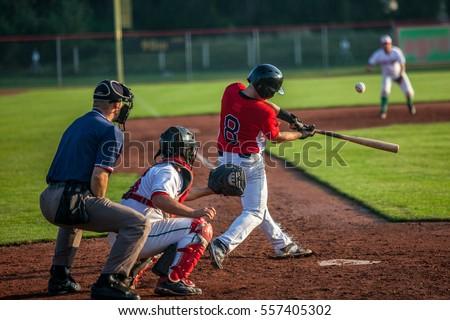 Baseball batter hits the ball Royalty-Free Stock Photo #557405302
