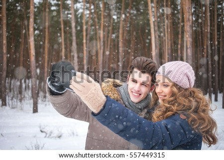 happy couple taking picture with smart-phone self ie stick on over winter background