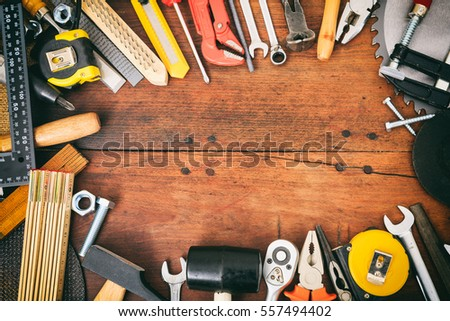 Variety of hand tools on a wooden table #557494402