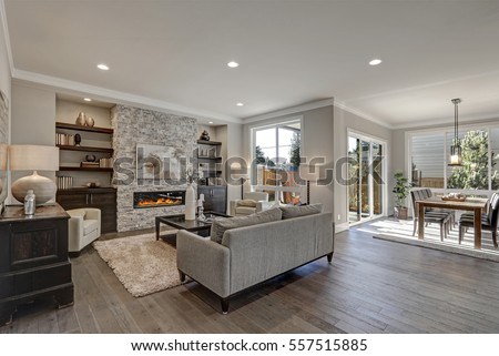 Living room interior in gray and brown colors features gray sofa atop dark hardwood floors facing stone fireplace with built-in shelves. Northwest, USA  Royalty-Free Stock Photo #557515885