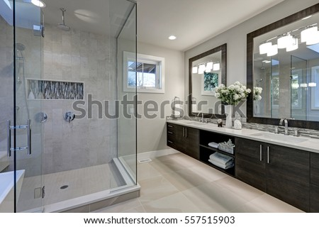 Spacious bathroom in gray tones with heated floors, walk-in shower, double sink vanity and skylights. Northwest, USA Royalty-Free Stock Photo #557515903