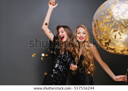 Brightfull expressions of happy emotions of two amazing girls celebrating party on black background. Luxury black dresses, smiling, golden tinsels, big balloon, long curly hair, stylish look #557556244