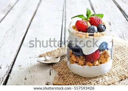 Healthy blueberry and raspberry parfait in a mason jar on a rustic white wood background #557593426
