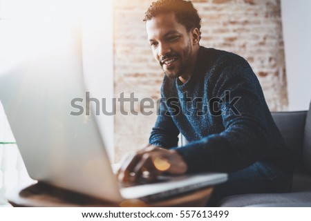 Cheerful African man using computer and smiling while sitting on the sofa.Concept of young business people working at home.Blurred background,flares Royalty-Free Stock Photo #557613499