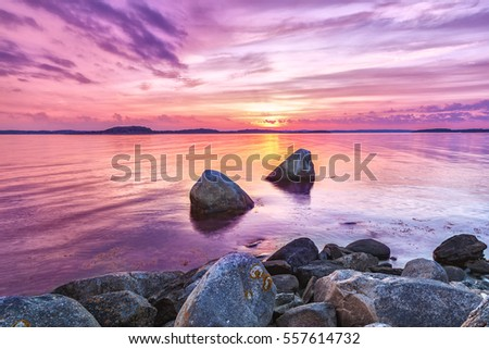 Picturesque sea sunset landscape with large stones at foreground. Violet toning of beautiful twilight scene. Color in nature concept.