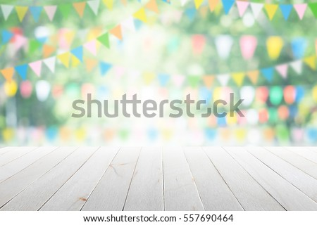 Empty wooden table with party in garden background blurred. Royalty-Free Stock Photo #557690464