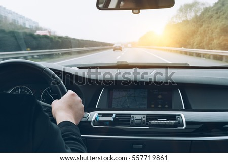 man driving car from rear view on the highway. Royalty-Free Stock Photo #557719861