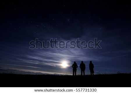 three mans stand on the hill at night with the big moon and stars