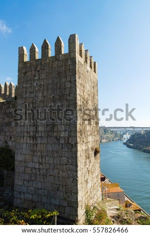 Portugal, Porto - OCTOBER 14, 2016: A view of the extreme tower of the medieval city wall and the river Douro #557826466